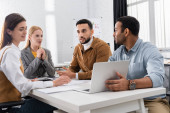 Multicultural business people sitting near laptop while working in office