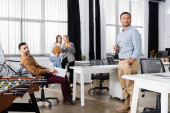 Multiethnic businesspeople standing near table soccer in office