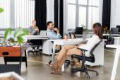 Mosolygó indiai üzletember ül közel kollégák és a kávé, hogy menjen az irodában