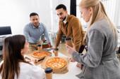 Mezirasoví obchodníci drží kávu jít blízko pizzy na stůl