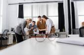 Multietničtí obchodníci s pizzou hrát stolní fotbal v blízkosti brýlí na rozmazané popředí v kanceláři