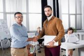 Multietničtí podnikatelé potřásají rukama a dívají se na kameru v kanceláři