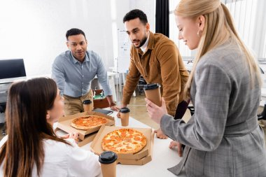 Interracial business people holding coffee to go near pizza on table stock vector