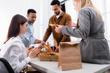Paper bag near multicultural business people holding pizza on blurred background in office stock vector
