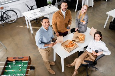 Overhead view of multiethnic business people smiling near pizza and coffee to go in office stock vector