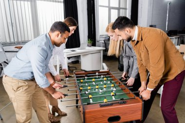 Interracial business people playing table soccer together in office stock vector
