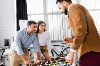 Multicultural business people looking at each other near table soccer in office stock vector