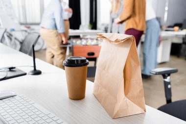 Cropped view of paper bag and coffee to go on table in office stock vector