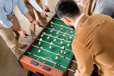 Overhead view of business people playing table soccer with colleagues in office stock vector