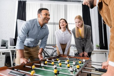 Positive multiethnic business people standing near table soccer in office stock vector