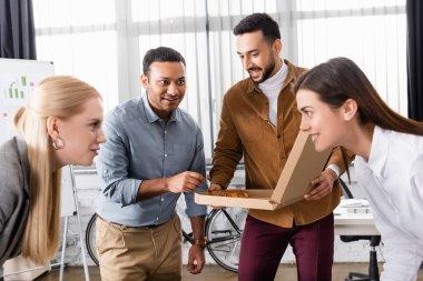Multiethnic businessmen holding pizza near businesswomen on blurred foreground in office stock vector