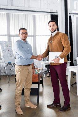 Multiethnic businessmen with laptop handshaking in office stock vector