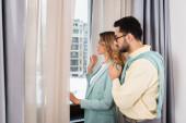 Seitenansicht eines gemischtrassigen Paares mit Blick auf Fenster im Hotelzimmer