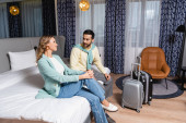 Smiling interracial couple sitting on bed near suitcases in hotel room
