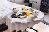 Newspaper near breakfast and drinks on table in hotel room