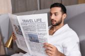 Cestovní život nápisy na novinách v rukou arabského muže v županu v hotelu