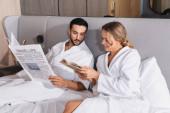 Lächelnde Frau zeigt muslimischen Freund mit Zeitung auf Hotelbett