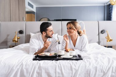 Smiling interracial couple looking at each other near breakfast on tray on hotel bed stock vector