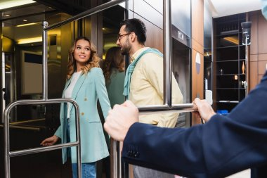 Smiling woman looking at muslim boyfriend near elevator and hotel porter on blurred foreground stock vector