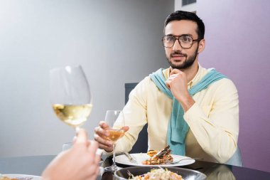 Arabian man holding glass of wine near girlfriend and dinner on blurred foreground in hotel stock vector