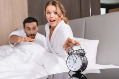 Alarm clock near excited woman and muslim man on hotel bed on blurred background stock vector
