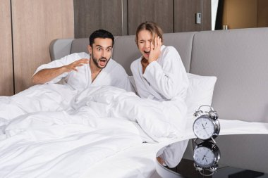 Stressed interracial couple in bathrobes sitting on bed near alarm clock on blurred foreground in hotel stock vector
