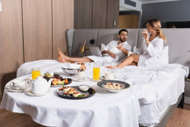 Tasty breakfast on table near interracial couple on bed in hotel stock vector