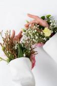 Oříznutý pohled na ženské ruce s květinami v rukávech bundy na šedém pozadí