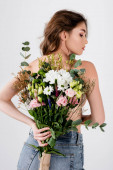 Back view of shirtless model holding bouquet isolated on grey