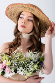 Young model in straw hat and different flowers in blouse isolated on grey