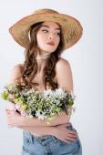 Kudrnatá žena ve slunečním klobouku a květiny v blůze pózování izolované na šedé