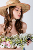 Young model in sun hat holding flowers isolated on grey