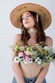 Göndör modell napszemüvegben, virágokkal a blúzban, elszigetelve a szürkén.