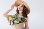 Fashionable model posing with flowers in blouse isolated on grey