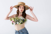 Trendy woman holding sun hat and posing with different flowers in blouse isolated on grey