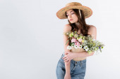Model in sun hat posing with flowers isolated on grey with copy space