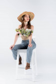 Stylish model with flowers in blouse posing on chair on grey background