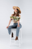Young woman in sun hat and flowers in blouse looking away on chair on grey background