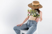 Woman with flowers in blouse and sun hat sitting on white chair isolated on grey