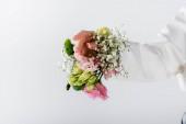 Ausgeschnittene Ansicht einer Frau mit verschiedenen Blumen im Ärmel des Blazers isoliert auf grau