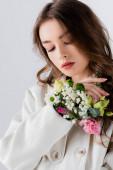 Mladý model v kabátě s květinami v rukávu stojí izolovaný na šedé