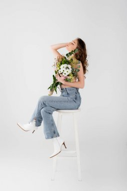 Shirtless woman in jeans holding flowers on chair isolated on grey stock vector