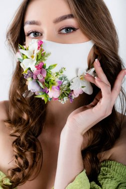 Portrait of brunette woman with flowers on medical mask looking at camera isolated on grey stock vector