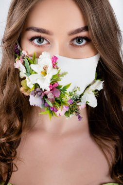 Portrait of woman with flowers on medical mask looking at camera isolated on grey stock vector