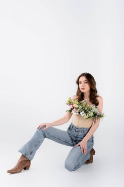 Young model in jeans, shoes and flowers in blouse on grey background stock vector