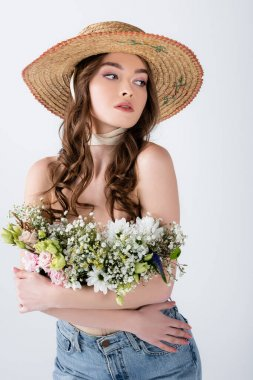 Curly woman in sun hat and flowers in blouse posing isolated on grey stock vector