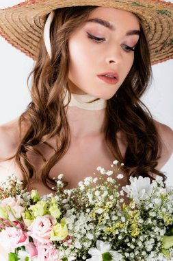 Young woman in stylish sun hat standing near bouquet isolated on grey stock vector