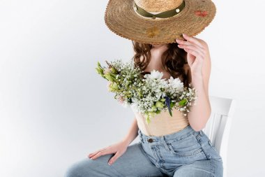 Woman with flowers in blouse covering face with sun hat isolated on grey stock vector