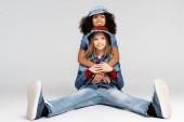 boldog afro-amerikai lány ölelését vidám, divatos barátja ül szürke