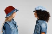 Seitenansicht von zwei interrassischen Mädchen in trendigen Klamotten und Hüten, die isoliert auf grau lächeln